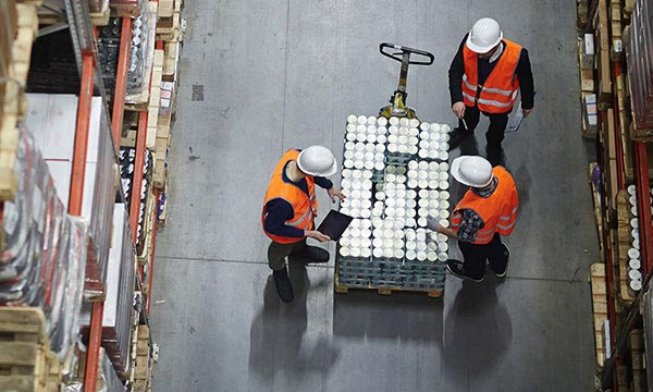 Pallet being loaded in Warehouse with workers checking goods